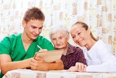 Ältere Frau mit den jungen Doktoren Stockbild