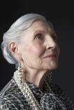 Ältere Frau mit den Perlen-Ohrringen, die oben schauen Stockfotografie