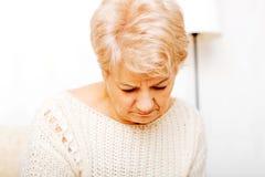 Ältere Frau mit der Krise, die auf Couch sitzt Stockbild