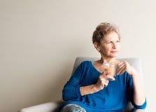 Ältere Frau mit der Tasse Tee schauend nachdenklich Lizenzfreie Stockfotos