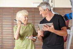 Ältere Frau mit Dummköpfen in der Turnhalle Lizenzfreies Stockfoto