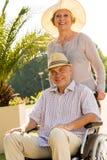 Ältere Frau mit Ehemann im Rollstuhl Stockfotos
