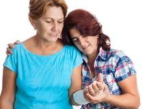 Ältere Frau mit einem gebrochenen Arm und ihrer Pflegekraft Stockbild
