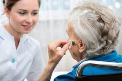 Ältere Frau mit einem Hörgerät stockbild