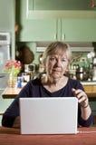 Ältere Frau mit einer Laptop-Computer lizenzfreies stockbild