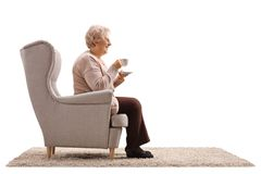Ältere Frau mit einer Schale gesetzt in einem Lehnsessel stockbilder