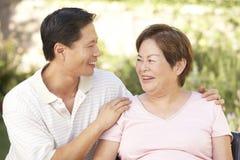 Ältere Frau mit erwachsenem Sohn im Garten Stockbild