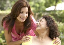 Ältere Frau mit erwachsener Tochter im Garten lizenzfreies stockfoto