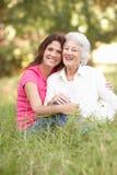 Ältere Frau mit erwachsener Tochter im Park Stockfotografie