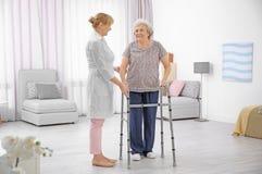 Ältere Frau mit gehendem Rahmen und Pflegekraft stockfotos