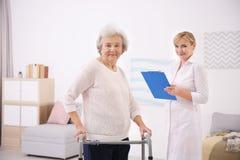 Ältere Frau mit gehendem Rahmen und Pflegekraft lizenzfreie stockfotos