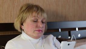 Ältere Frau mit geschlossenen Augen sitzt auf dem Sofa und hört Musik stock footage
