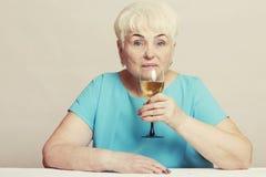 Ältere Frau mit Glas Weißwein Stockfotos