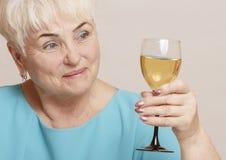 Ältere Frau mit Glas Weißwein Lizenzfreies Stockfoto
