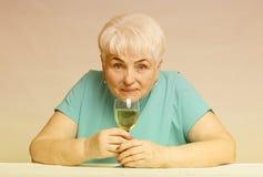 Ältere Frau mit Glas Weißwein Stockbilder