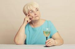 Ältere Frau mit Glas Weißwein Stockfotografie