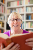 Ältere Frau mit Glaslesebuch zu Hause Lizenzfreies Stockbild