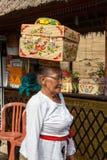 Ältere Frau mit Korb auf dem Kopf Stockbild