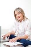 Ältere Frau mit Laptop und Ablage stockfotografie