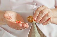 Ältere Frau mit Medizin in einer Hand Stockbild