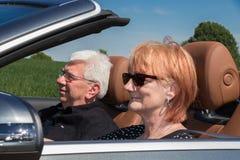 Ältere Frau mit Partnerautofahren lizenzfreie stockfotos