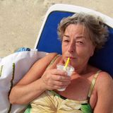Ältere Frau mit pinacolada Lizenzfreie Stockfotografie