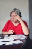 Ältere Frau mit Rechnungen Stockfotos