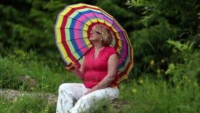 Ältere Frau mit Regenschirm sitzt auf einem gefallenen Baum im Wald stock footage