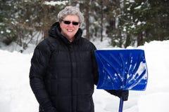 Ältere Frau mit Schnee-Schaufel Stockbild