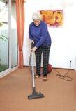 Ältere Frau mit Staubsauger Stockfoto