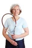 Ältere Frau mit Tennisschläger stockfotografie