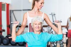 Ältere Frau mit Trainer in anhebendem Dummkopf der Turnhalle Stockfoto