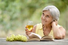 Ältere Frau mit Wein und Buch Stockfotografie