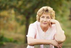 Ältere Frau nahe einem Tor zum Garten Stockbilder