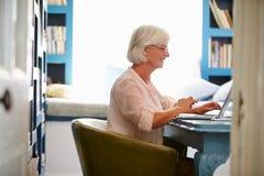 Ältere Frau am Schreibtisch, der im Innenministerium mit Laptop arbeitet stockfoto