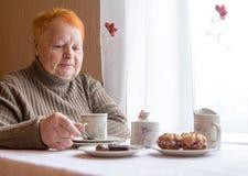 Ältere Frau sitzt bei Tisch und trinkt Tee mit Kuchen Stockbilder