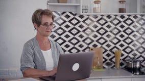 ?ltere Frau sitzt am Tisch und arbeitet unter Verwendung der Digitalrechnertechnologie stock video