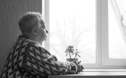 Ältere Frau sitzt und schaut heraus das Fenster Stockfotografie