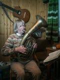 Ältere Frau spielt auf einem Horn Lizenzfreie Stockfotografie