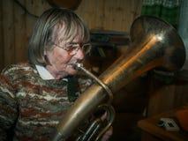 Ältere Frau spielt auf einem Horn Lizenzfreies Stockfoto