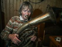 Ältere Frau spielt auf einem Horn Stockfotos