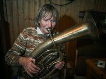 Ältere Frau spielt auf einem Horn Stockbild