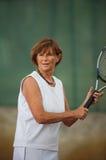 Ältere Frau spielt Tennis lizenzfreie stockfotografie