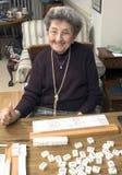 Ältere Frau am Spieltisch Stockfotografie