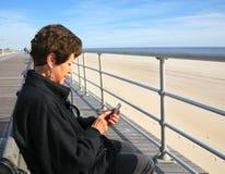 Ältere Frau Texting am Strand Stockbild
