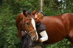 Ältere Frau und brauner Pferdeportrait im Wald Stockbild