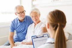 Ältere Frau und Doktor mit Klemmbrett am Krankenhaus Stockfoto