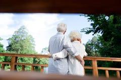 Ältere Frau und Ehemann, welche die Ansicht von schönem See und von Wald genießt lizenzfreie stockfotos