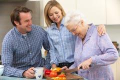 Ältere Frau und Familie, die zusammen Mahlzeit vorbereitet Lizenzfreie Stockfotos