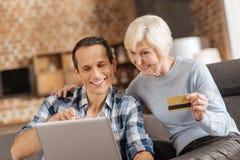 Ältere Frau und ihr Sohn, die zusammen on-line-kaufen tut lizenzfreies stockfoto